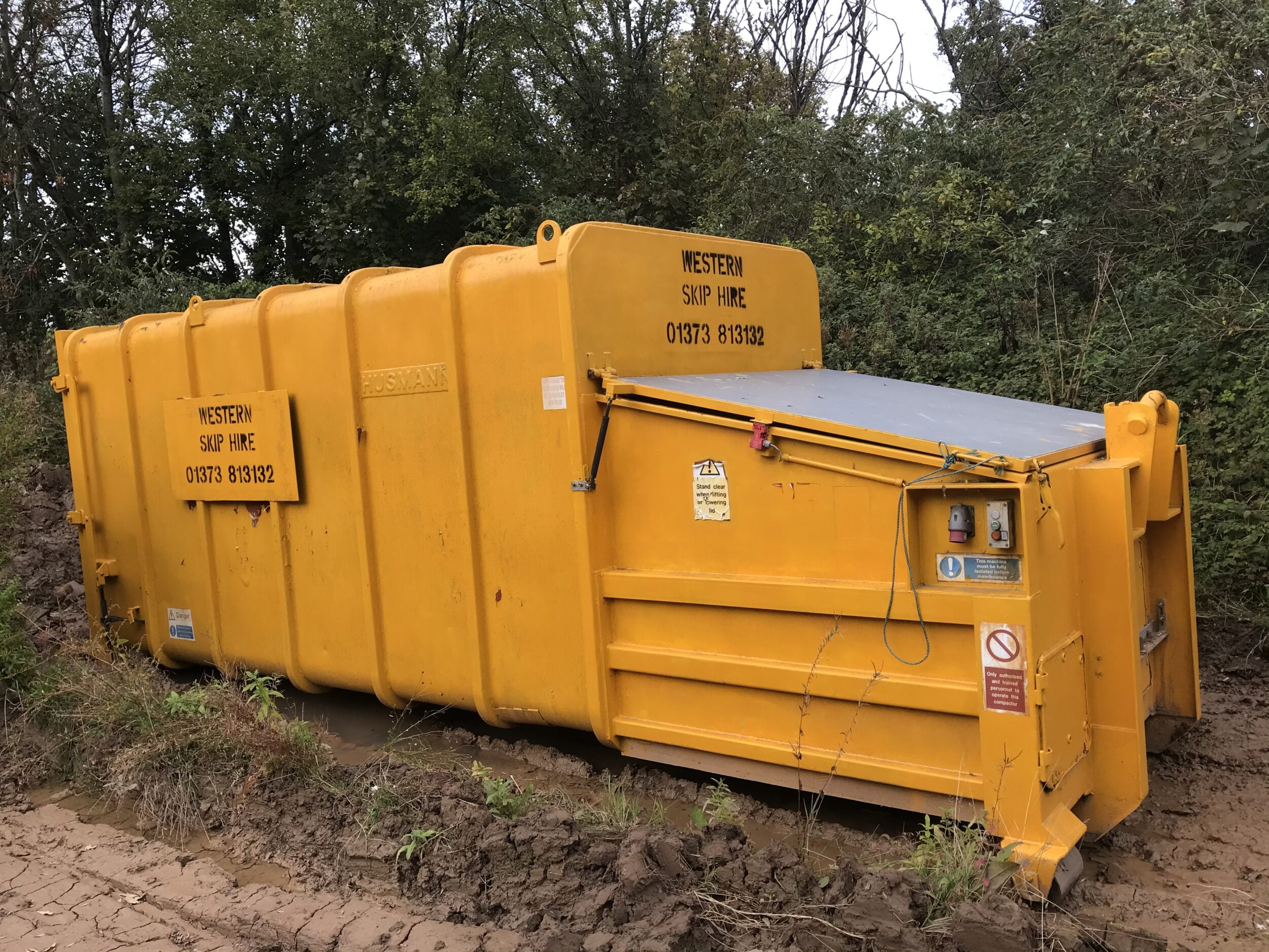 Large Yellow Compactor Skip. Western Skip Hire, Skip Hire, Sweeper Hire, Aggregates, Recycled Waste Stone and Concrete. Westbury, Frome, Somerset, Wiltshire.